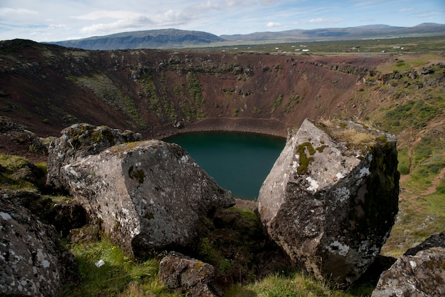 Volcanic crater lake with moss and lichen covered boulders