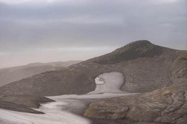 Вулканический пейзаж с ледником, скалами и пеплом на туристической тропе фиммвордухальс. исландия.