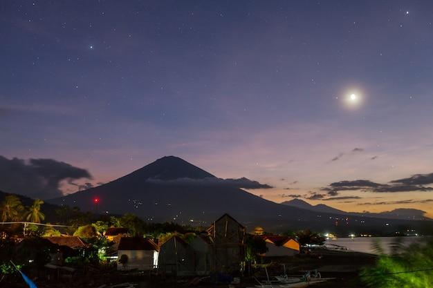 夜のインドネシア、バリ島のアグン火山とアメッドビーチ