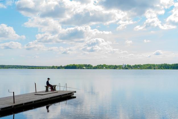 ヴォルガ川、ロシア、2021年5月28日。釣り竿を持った少年が夏に川で釣りをしています。