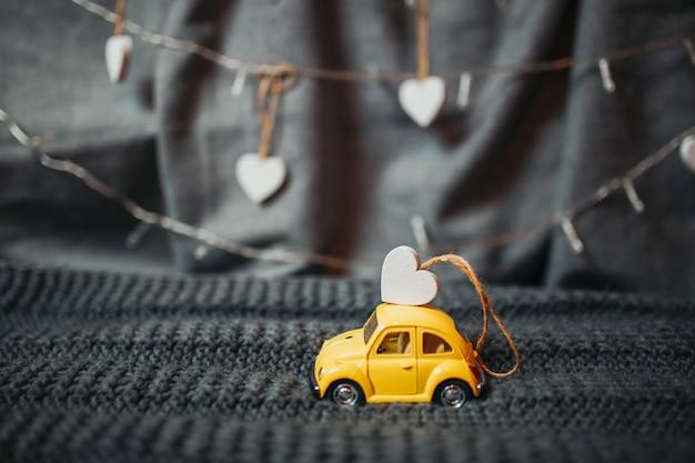 Открытка ко дню святого валентина. желтый игрушечный автомобиль с крошечным сердечком на крыше. игрушечный желтый volkswagen beetle с гирляндой огней на заднем плане.