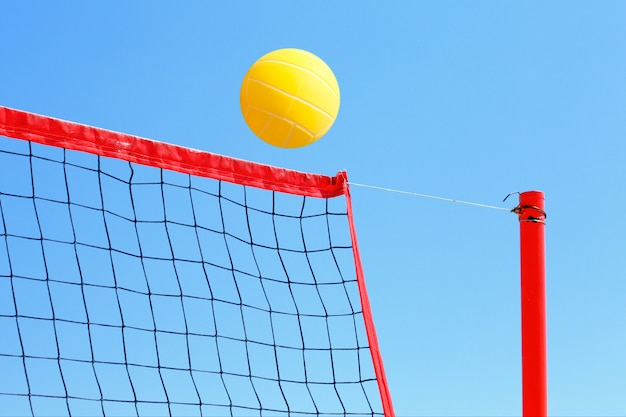 Volleyball on the beach, net and yellow ball on blue sky background.