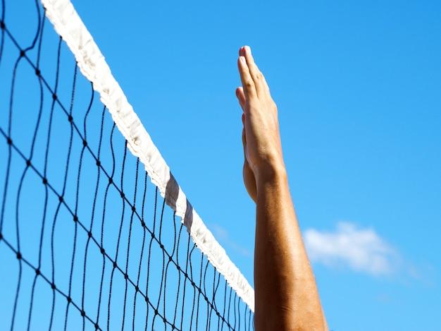 Волейбольная сетка на тропическом пляже. мужские руки бьют по мячу.