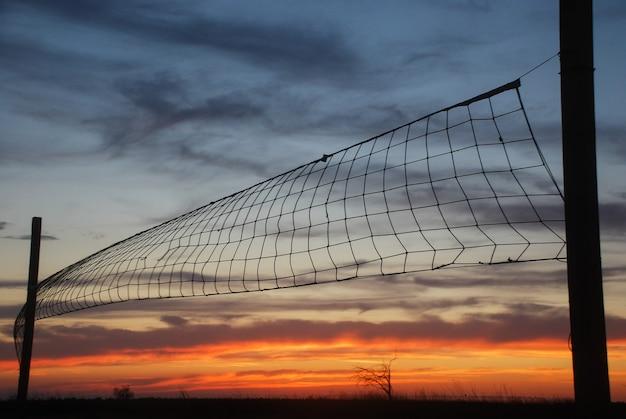 夕焼け空の背景にバレーボールネット