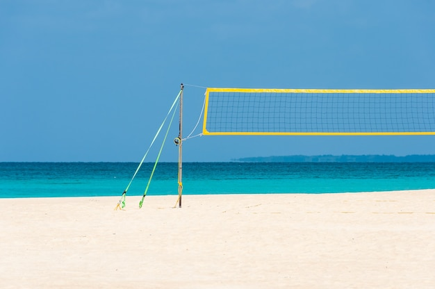 Volleyball net on a paradisiacal white beach sand, turquoise sea on a beautiful sunny day.