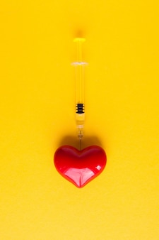 Объемное сердце со шприцами на розовом фоне. концепция поддержки пациентов с заболеваниями сердца