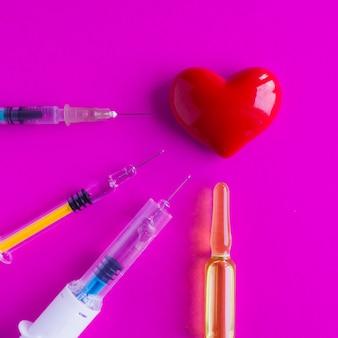 Объемное сердце со шприцами на розовой поверхности. концепция поддержки пациентов с заболеваниями сердца