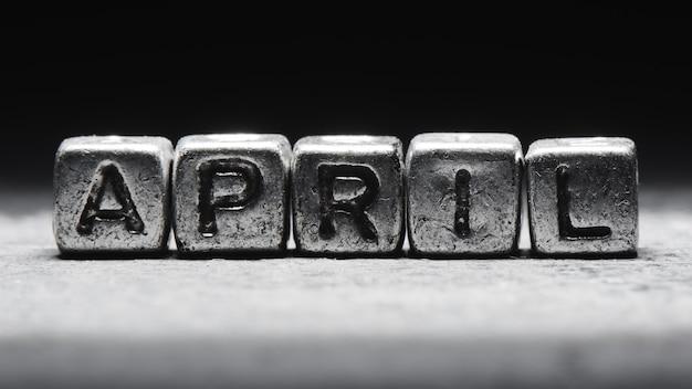 Объемная надпись апрельских серебряных металлических кубиков на темно-черном фоне. календарь крайних сроков, личное расписание и тайм-менеджмент