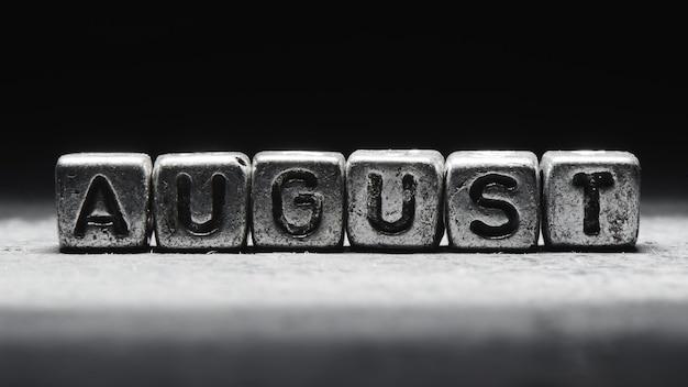 Объемная надпись август серебряными металлическими кубиками на темно-черном фоне. календарь крайних сроков, личное расписание и тайм-менеджмент