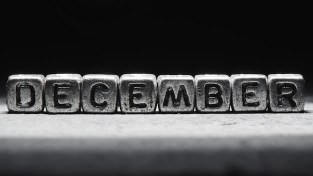 Объемная надпись декабрь серебряные металлические кубики на темно-черном фоне. календарь крайних сроков, личное расписание и тайм-менеджмент