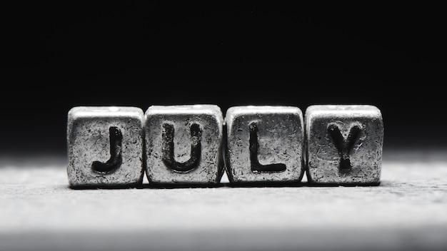 Объемная надпись июльские серебряные металлические кубики на темно-черном фоне. календарь крайних сроков, личное расписание и тайм-менеджмент