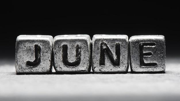 Объемная надпись июньские серебряные металлические кубики на темно-черном фоне. календарь крайних сроков, личное расписание и тайм-менеджмент