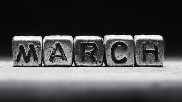 Объемная надпись мартовскими серебряными металлическими кубиками на темно-черном фоне. календарь сроков, личное расписание и тайм-менеджмент, семь дней в неделю