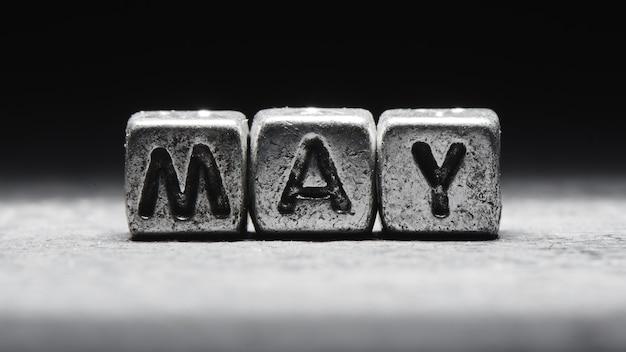 Объемная надпись may серебряными металлическими кубиками на темно-черном фоне. календарь крайних сроков, личное расписание и тайм-менеджмент