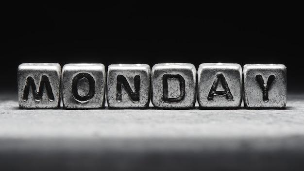 Объемная надпись понедельника серебряными металлическими кубиками на темно-черном фоне. календарь сроков, личное расписание и тайм-менеджмент, семь дней в неделю