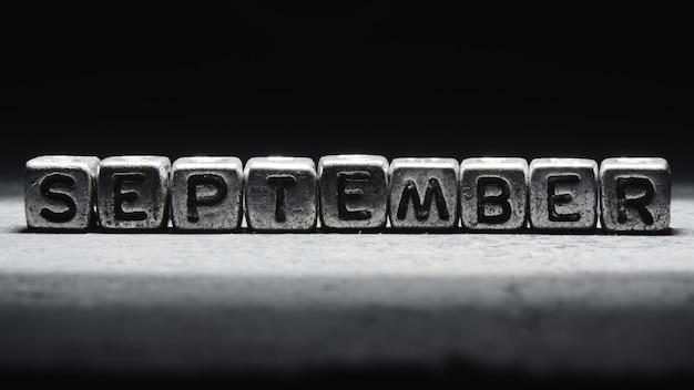 Объемная надпись сентябрьские серебряные металлические кубики на темно-черном фоне. календарь крайних сроков, личное расписание и тайм-менеджмент