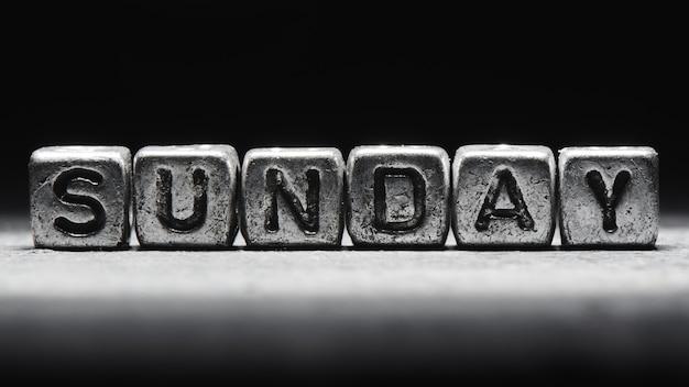 Объемная надпись воскресенья серебряные металлические кубики на темно-черном фоне. календарь сроков, личное расписание и тайм-менеджмент, семь дней в неделю