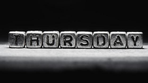Volumetric inscription thursday silver metal cubes on a dark black background. deadline calendar, personal scheduling and time management, seven days a week