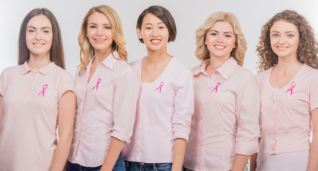 Voluntary cheerful women wearing pink ribbons to support