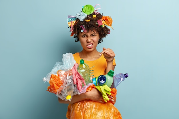 Добровольная бесплатная помощь. раздраженная чернокожая женщина, обеспокоенная проблемой загрязнения окружающей среды, несет мешок для мусора с переработанным пластиком, стискивает зубы от раздражения, изолирована на синей стене