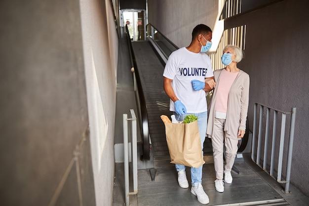 Волонтер и пенсионер выходят из супермаркета рука об руку и смотрят друг на друга