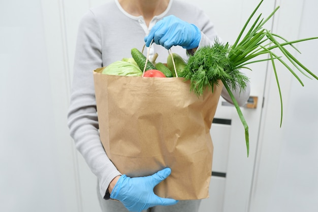 Volunteer in blue gloves holds food donation package vegetables to help the poor. donat box with foodstuffs