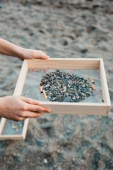 Volontario che raccoglie le sigarette in spiaggia