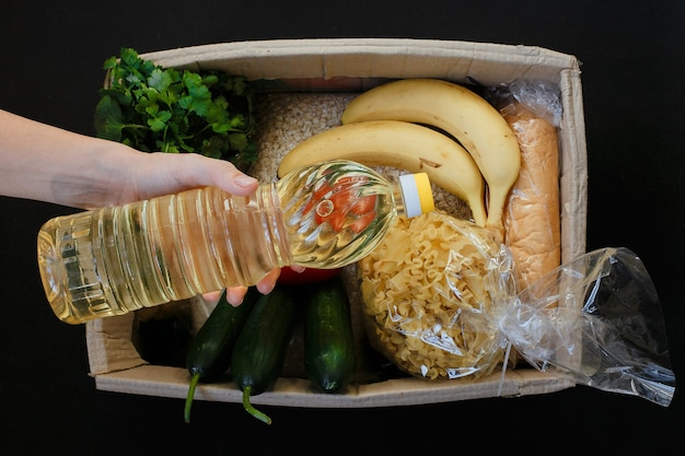 屋内の寄付ボックスに食べ物を集めるボランティア黒い背景の上のフードボックスの上面図 Premium写真