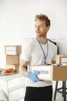 Il volontario raccoglie le cose dalle donazioni. guy confeziona scatole con le cose. l'uomo confronta la dotazione.