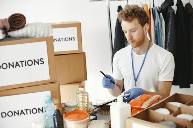 ボランティアは寄付から物を集めます。男は箱に物を詰めます。男は寄付を比較します。