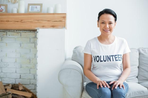 자원 봉사의 날. 카메라를 응시하고 무릎에 손을 얹는 동안 소파에 앉아 게이 낙관적 여성 자원 봉사자