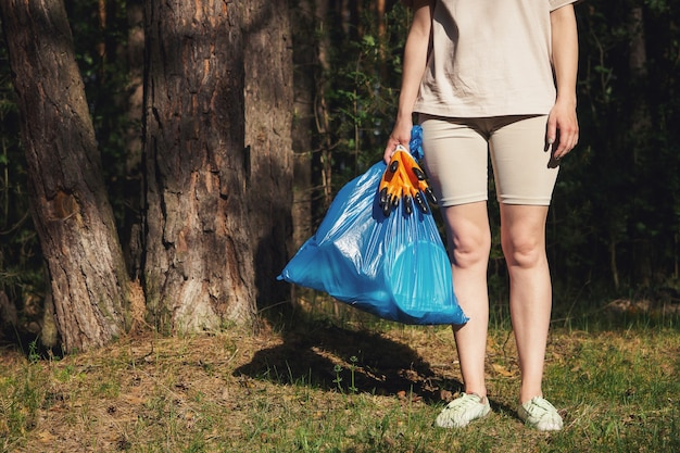 A volunteer and eco activist collects garbage in bags, in the forest, close-up. recycling of plastic waste, environmental protection. protecting the planet from debris. ecology concept.