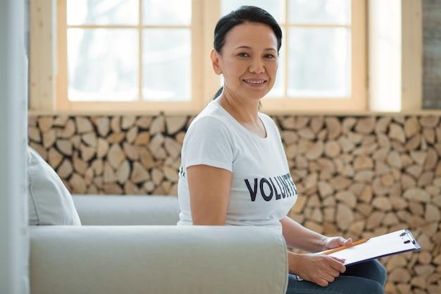 자원 봉사 경험. 카메라를보고 앉아있는 동안 클립 보드를 들고 행복 즐거운 여성 자원 봉사자