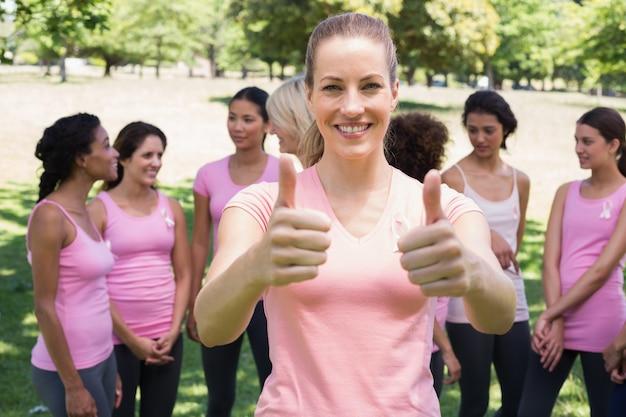 유방암 캠페인에서 자원 봉사자 몸짓 엄지 손가락