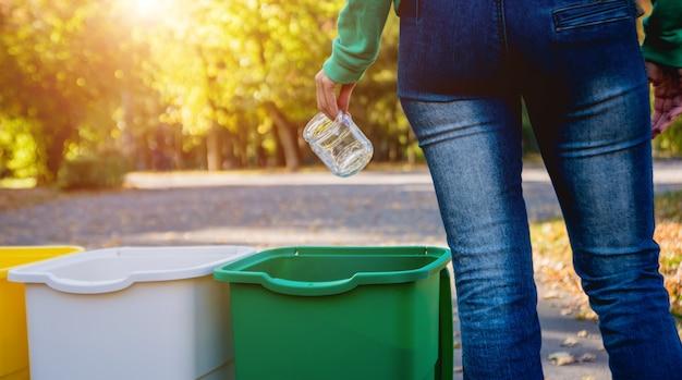 Волонтер девушка разбирает мусор на улице парка. концепция утилизации.