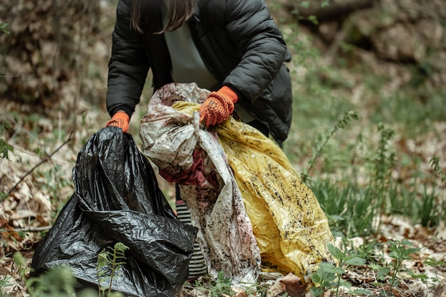 A volunteer girl with a garbage bag cleans up garbage in the forest.