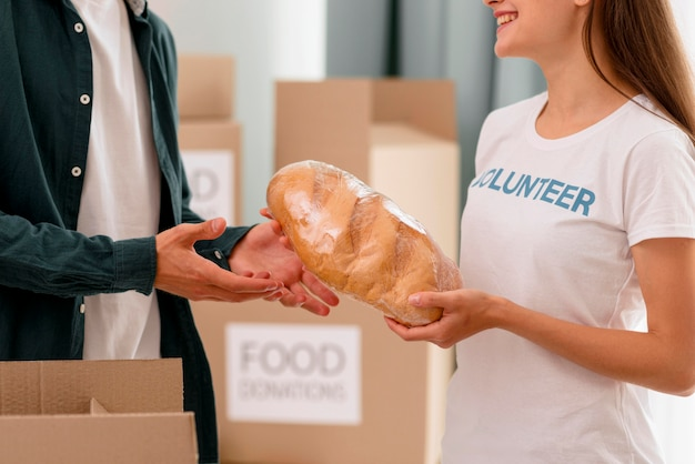Volunteer giving out bread for person in need