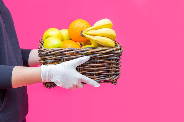 Volunteer in gloves holds basket of grocery products with fruits