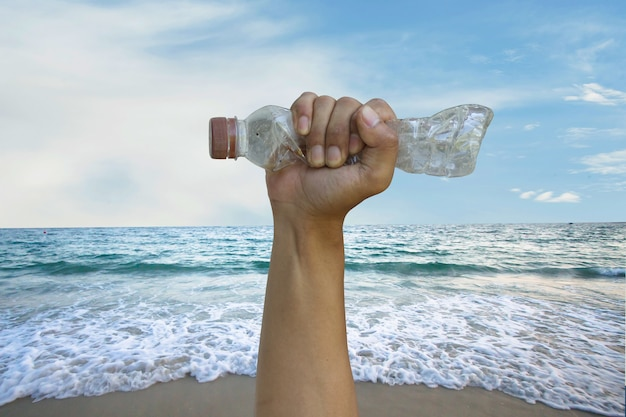 Volunteer hand grab a plastic bottle with sea wave on background