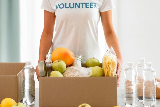 Волонтер держит коробку с едой для пожертвования