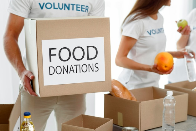 Volunteer holding box with provisions for charity