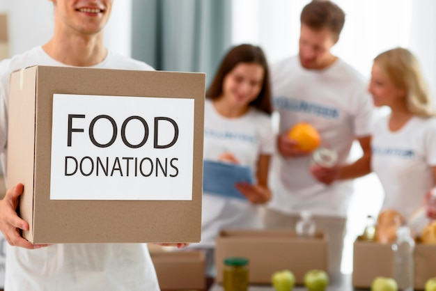 Volunteer holding box with provisions for donation