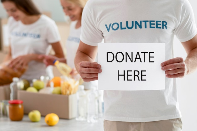 Волонтер держит плакат с инструкциями по пожертвованию