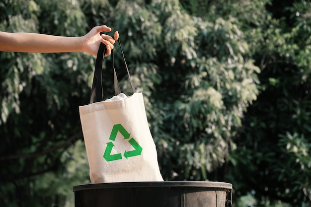 The volunteer holding a plastic bag in to a bin.