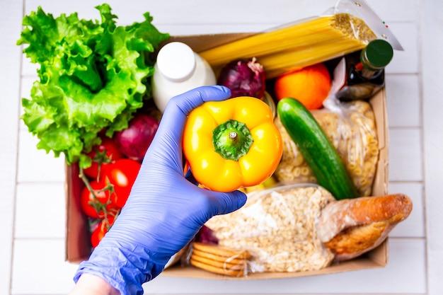 Волонтер в перчатках дает еду в картонной коробке для пожертвований