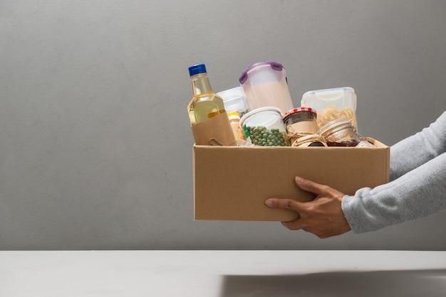 Волонтер в перчатках держит еду в картонной коробке для пожертвований с различной едой.