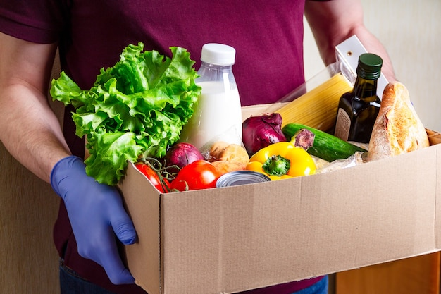 Волонтер в перчатках держит еду в картонной коробке для пожертвований