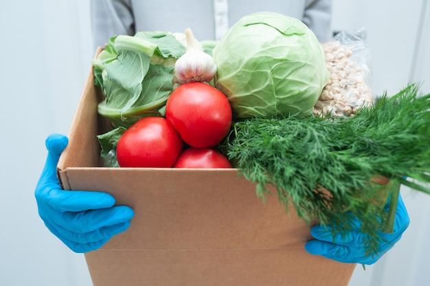 Волонтер в перчатках держит коробку для пожертвований овощей, чтобы помочь больным или бедным