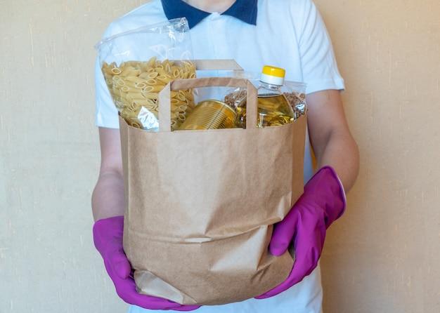 Волонтер в защитных перчатках кладет еду в ящик для пожертвований. работник работника доставляющего покупки на дом в красной коробке упаковки жилета с едой. служба карантинной пандемии коронавируса.
