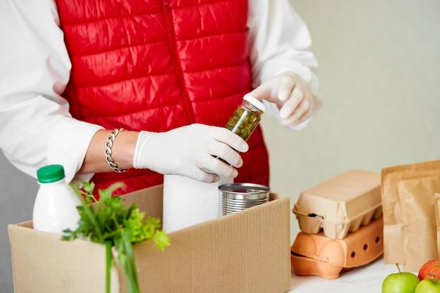 Доброволец в защитной медицинской маске и перчатках кладет еду в ящик для пожертвований.